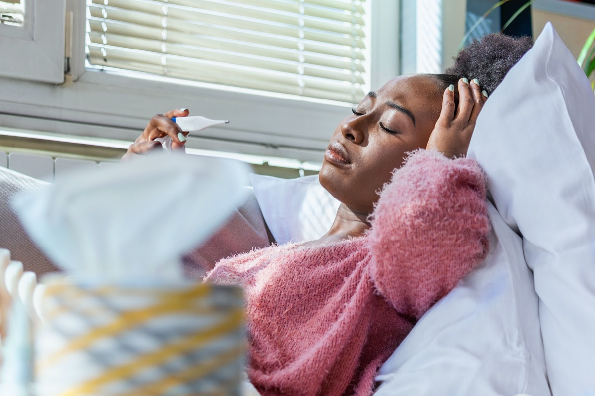 Woman being sick having flu lying on sofa looking at temperature on thermometer.