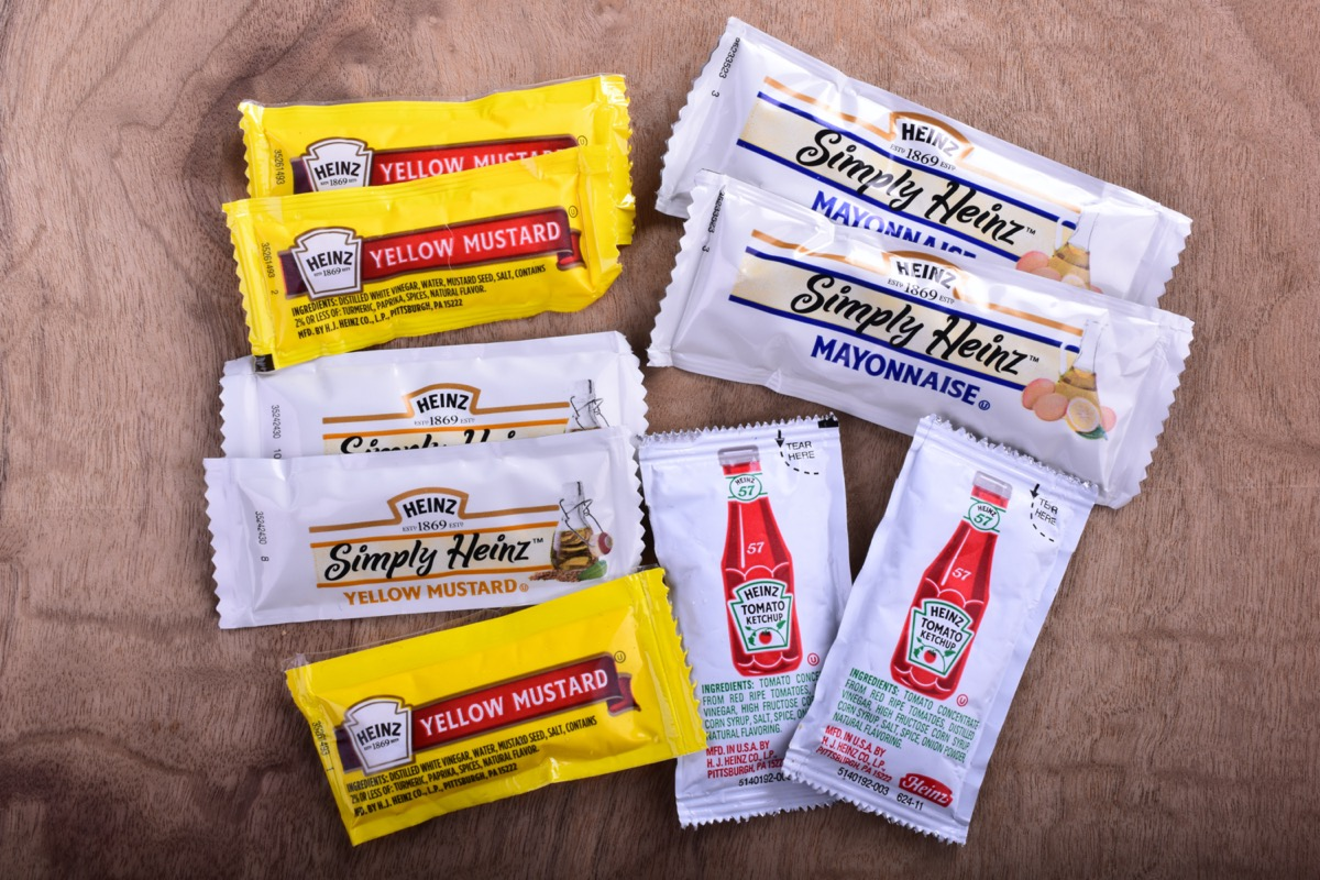Various single serve packets of Heinz products including ketchup mayo and yellow mustard on a cherry wood countertop.