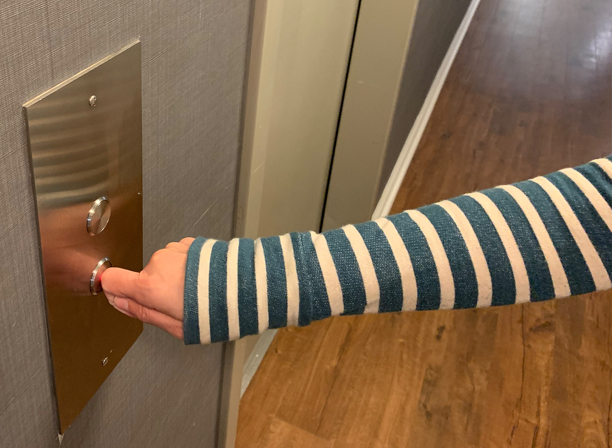 woman's hand pushing elevator button