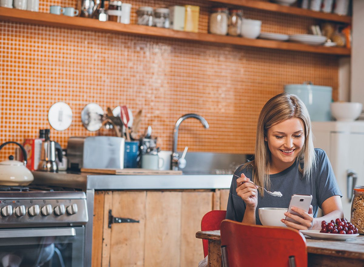 woman alone in kitchen looking at phone while eating