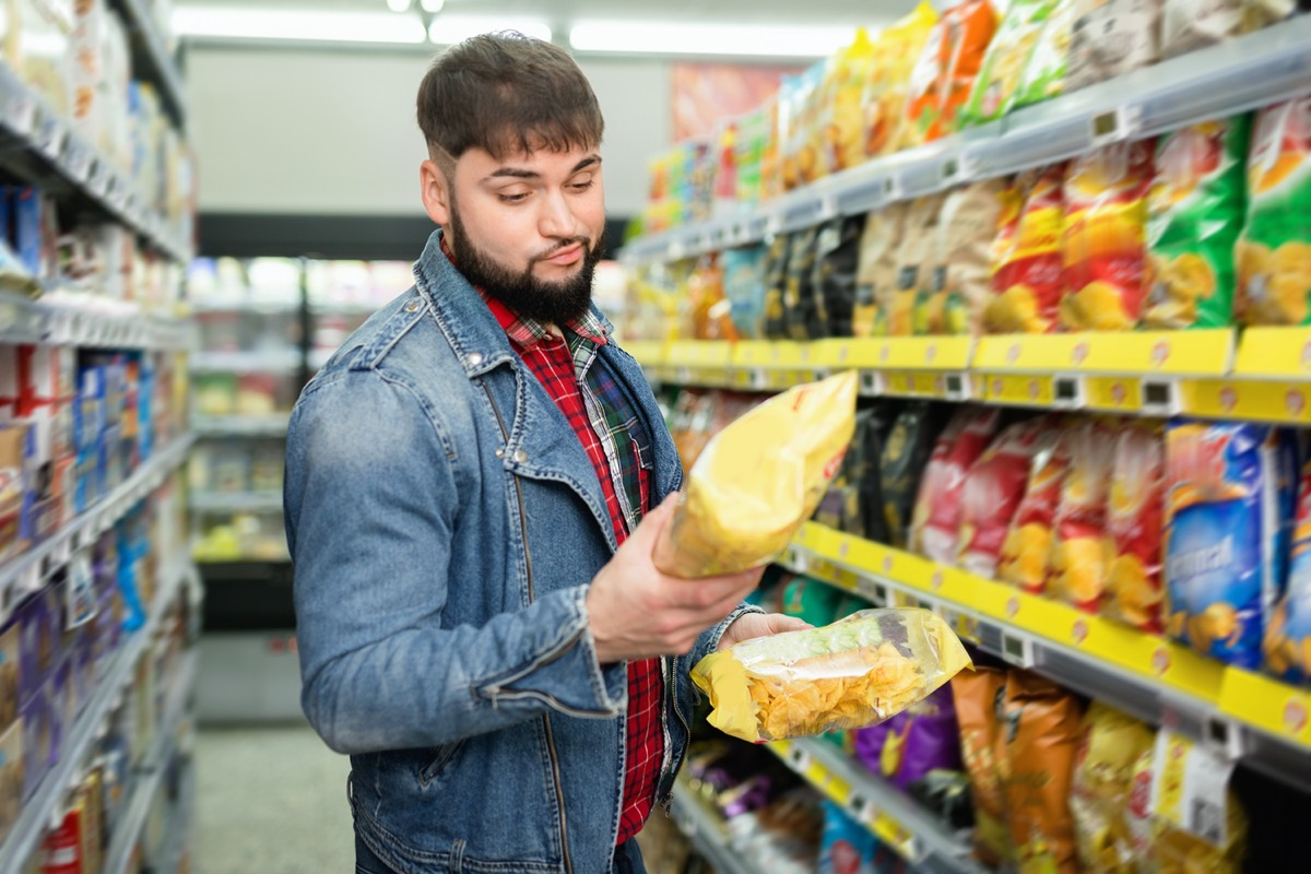 smiling glad friendly bearded guy choosing potato chips at grocery store