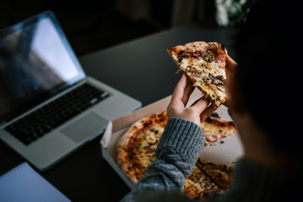 Eating pizza and social networking with a laptop.