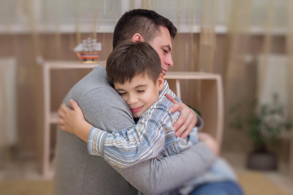 Father, son in emotional embrace of tears and joy