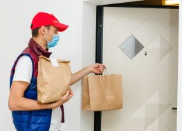 Delivery man holding paper bag with food on white background, food delivery man in protective mask