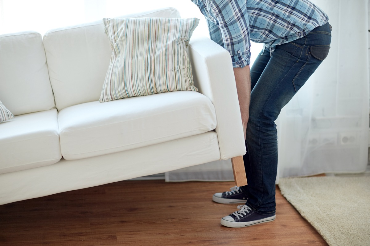 male lifting up sofa or couch