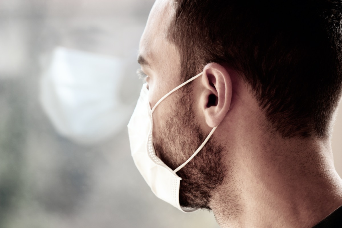 Photo of a young white man with medical face mask looking out of the window during coronavirus quarantine. Reflection of his face in the window.