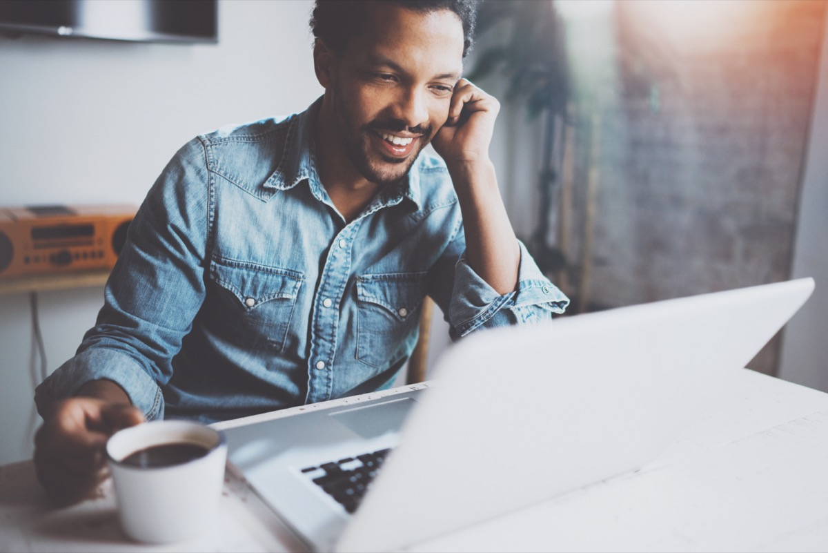 Happy bearded African man making video conversation via modern laptop with partners while holding white cup black coffee at home