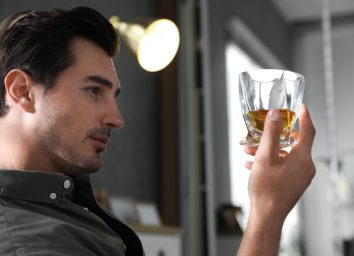 man with glass of whiskey at home