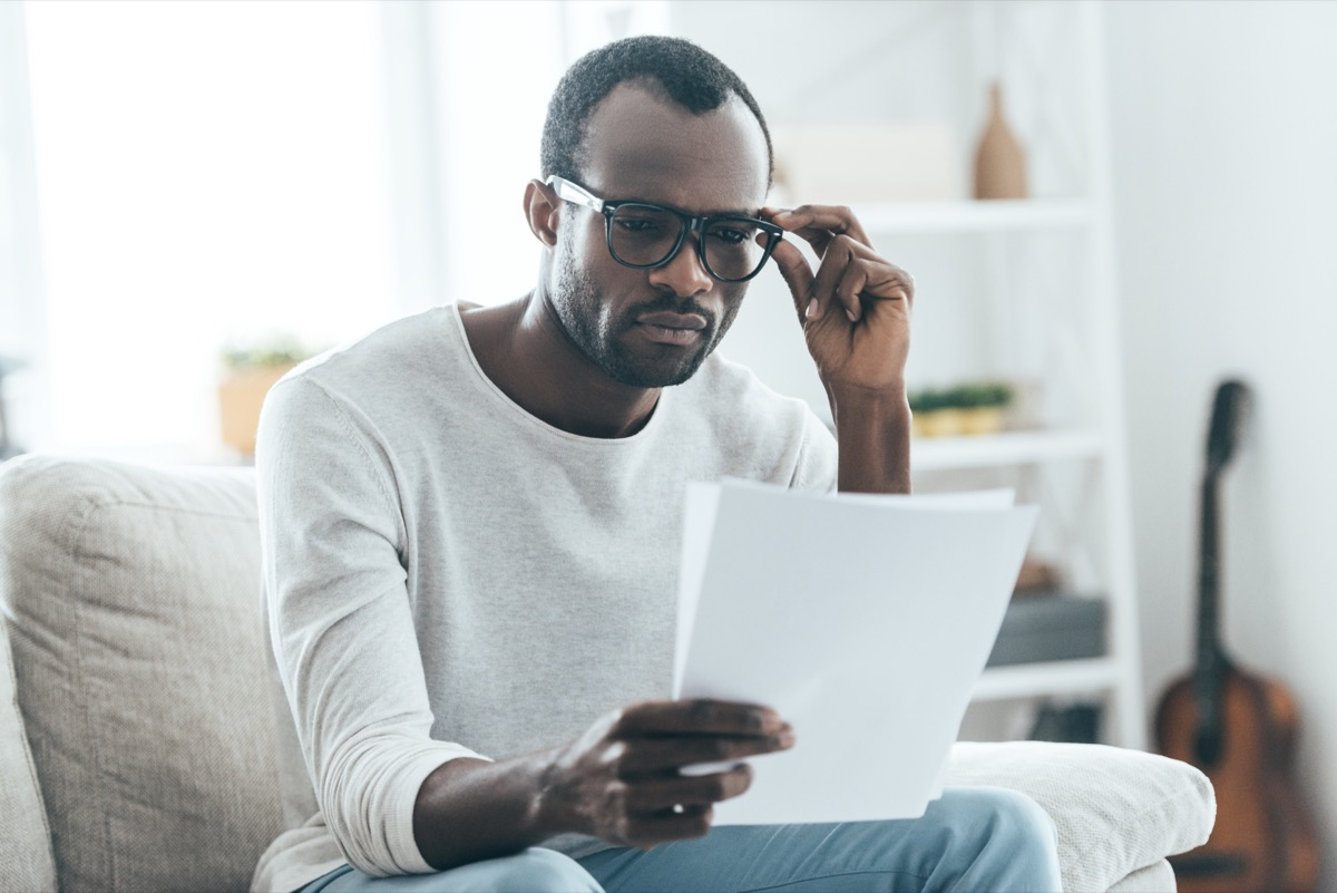 man reading documents and touching eyeglasses with his hand while sitting on the sofa at home