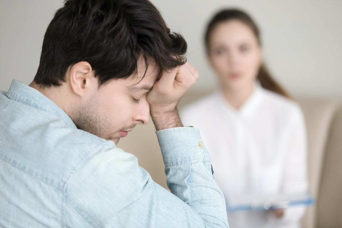 guy touching his forehead, having a headache or migraine, overworked businessman feeling tired, stressed and exhausted, female doctor, nurse or colleague standing in the background