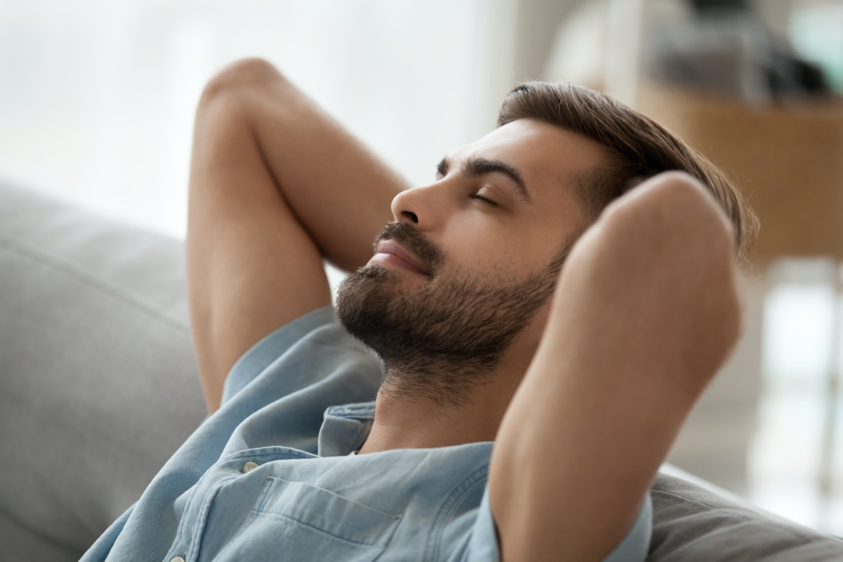 Relaxed happy young man resting having nap on comfortable couch breathing fresh air