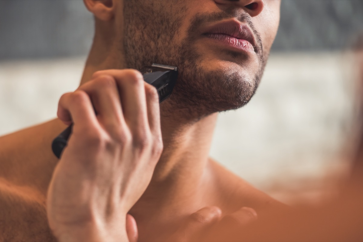 man shaving using an electric razor