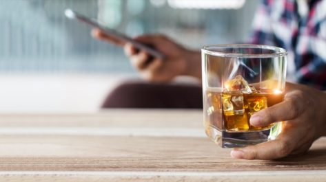 Man relaxing with bourbon whiskey drink alcoholic beverage in hand and using mobile smartphone