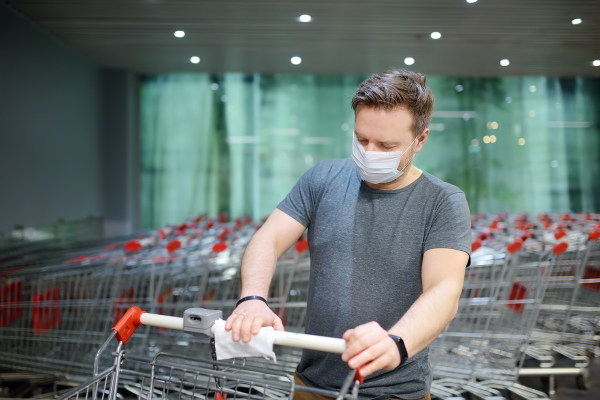 Man wearing disposable medical face mask wipes the shopping cart handle with a disinfecting cloth in supermarket