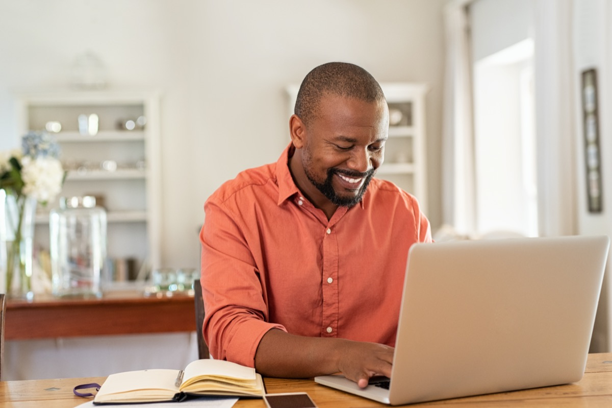 Smiling black man using laptop at home in living room. Happy mature businessman send email and working at home