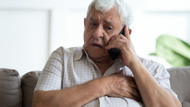 Upset older man touching chest, calling emergency, talking on phone, unhappy mature male having heart attack