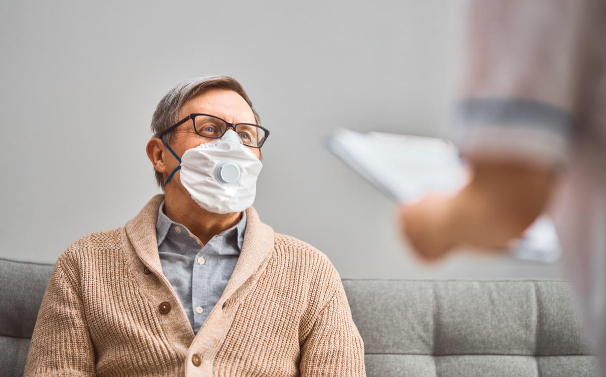 Doctor and senior man wearing facemasks during coronavirus and flu outbreak
