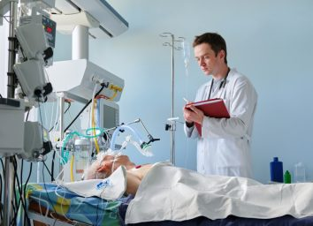 Intensive care caucasian doctor examines intubated critical stance patient writing notes to case report in intensive care department