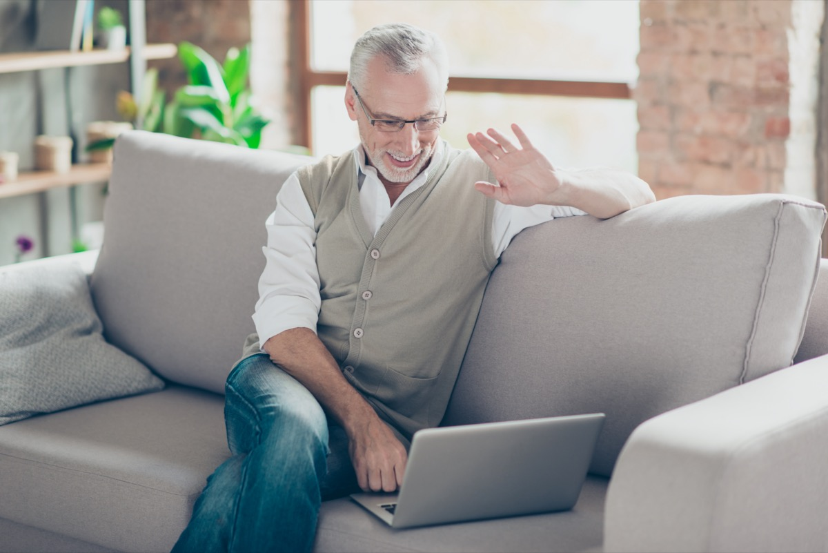 Cheerful excited joyful intelligent clever glad relaxed grandpa using netbook telling relatives friends