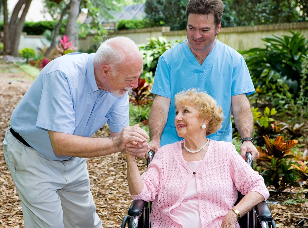 Senior husband visiting his disabled wife on the grounds of the nursing home while a nurse pushes her wheelchair.