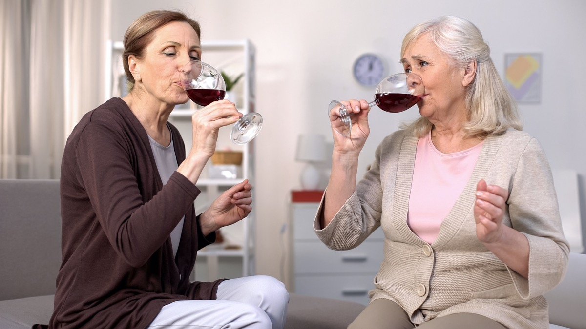 Two elderly women drinking red wine from glasses, friends communication at home