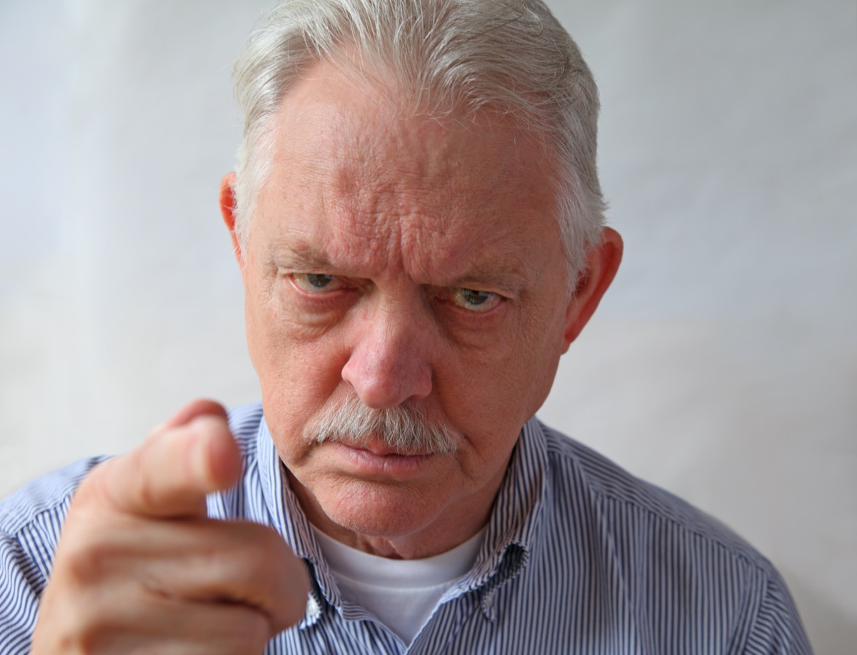 An angry senior points an accusing finger