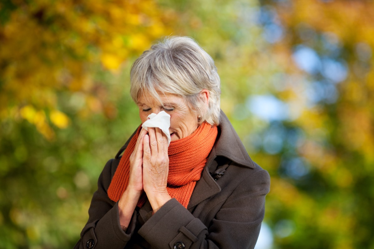 Senior woman in jacket suffering from cold in park