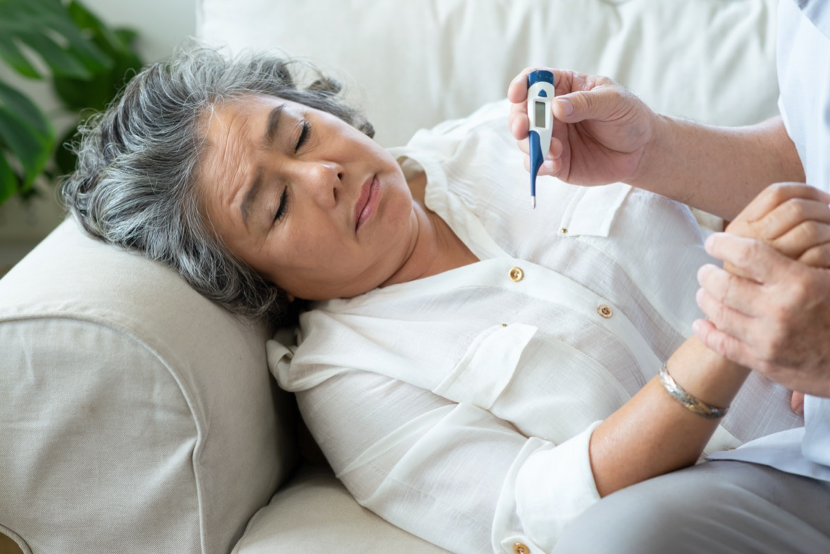 Elderly woman having cold during lie down on couch while Senior man checking temperature of his wife with digital thermometer in house