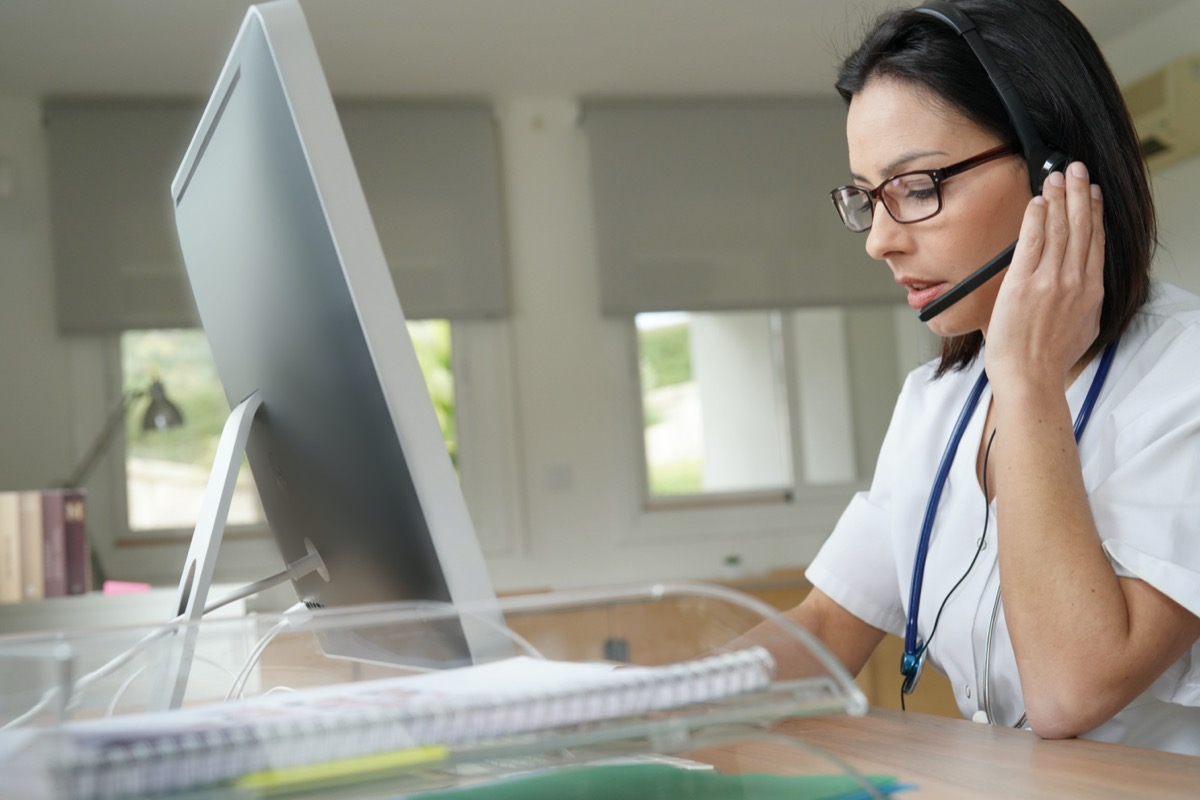 Medical secretary typing report on desktop computer