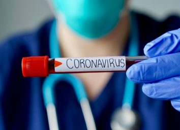 Nurse wearing respirator mask holding a positive blood test result for the new rapidly spreading Coronavirus