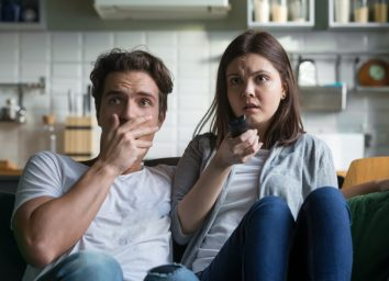 Scared millennial couple watching horror movie on tv holding remote control at home