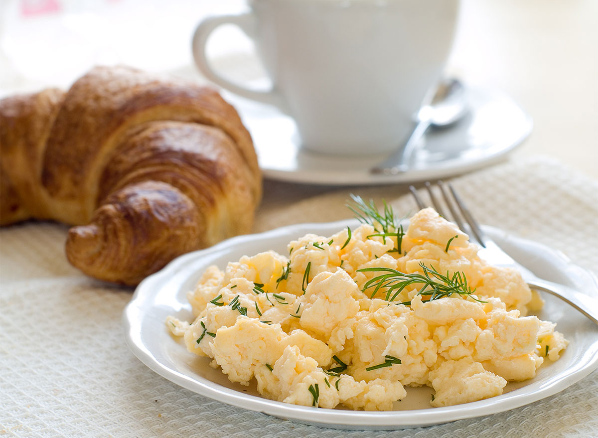 plate of scrambled eggs with croissant and coffee