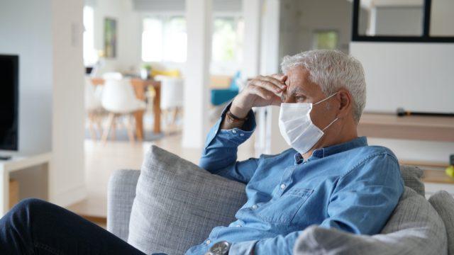 Senior man at home wearing protection mask