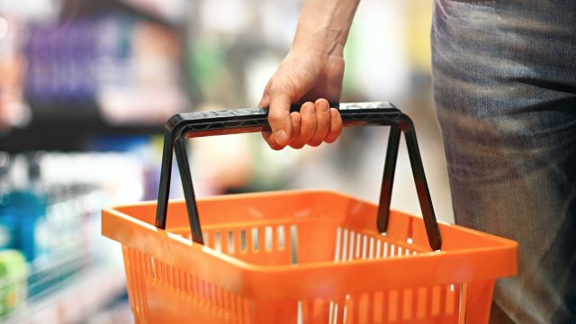 Men's hand holding an empty basket in the supermarket