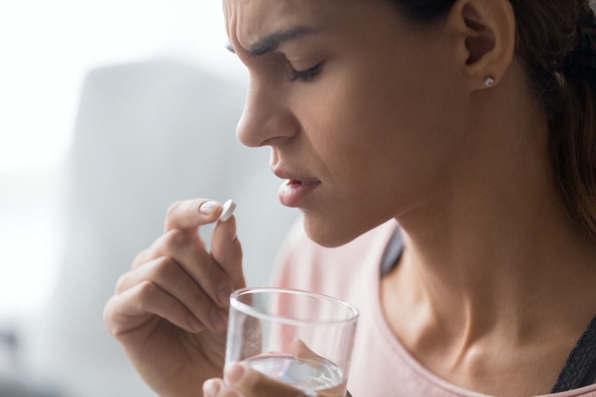 Unhappy woman side view holds tablet and glass of water