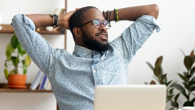 man take break at workplace relaxing finished work, happy black professional employee enjoy success rest from computer feeling stress relief peace of mind sit at desk