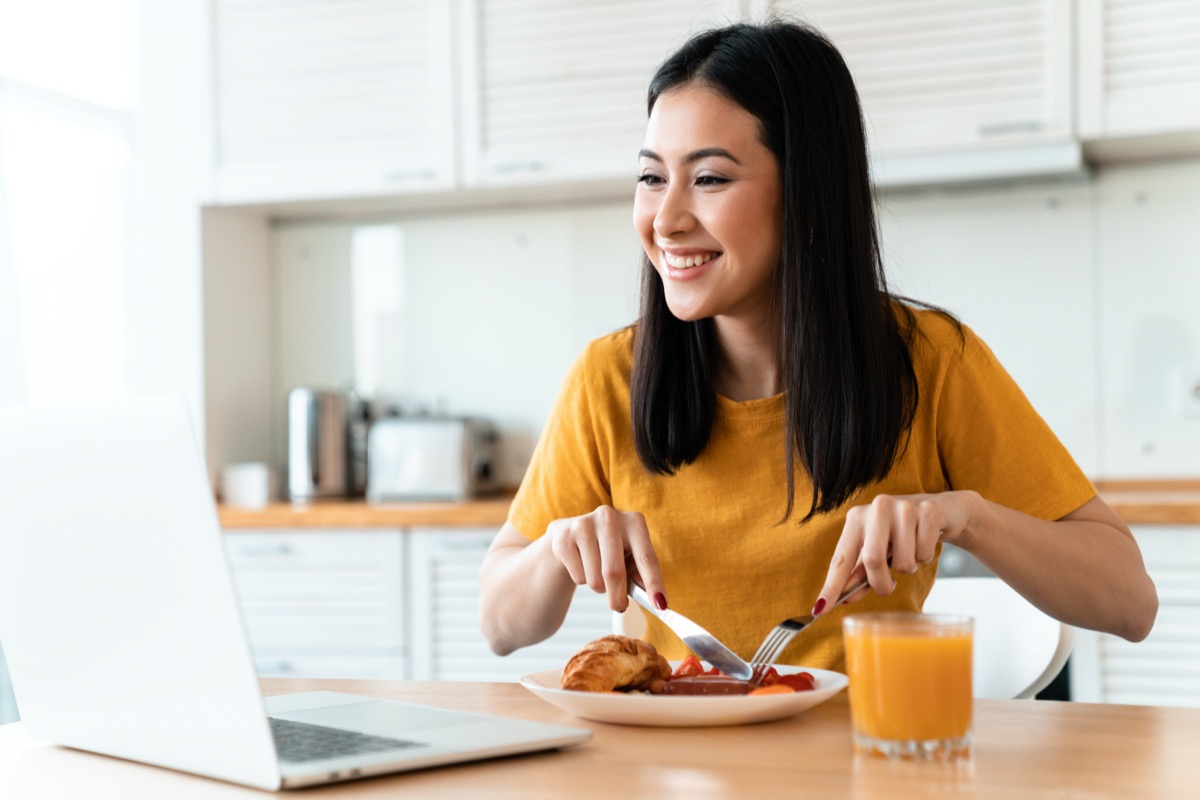 Image of a beautiful positive cheerful brunette young woman at the kitchen indoors at home using laptop computer have a dinner watch videos.