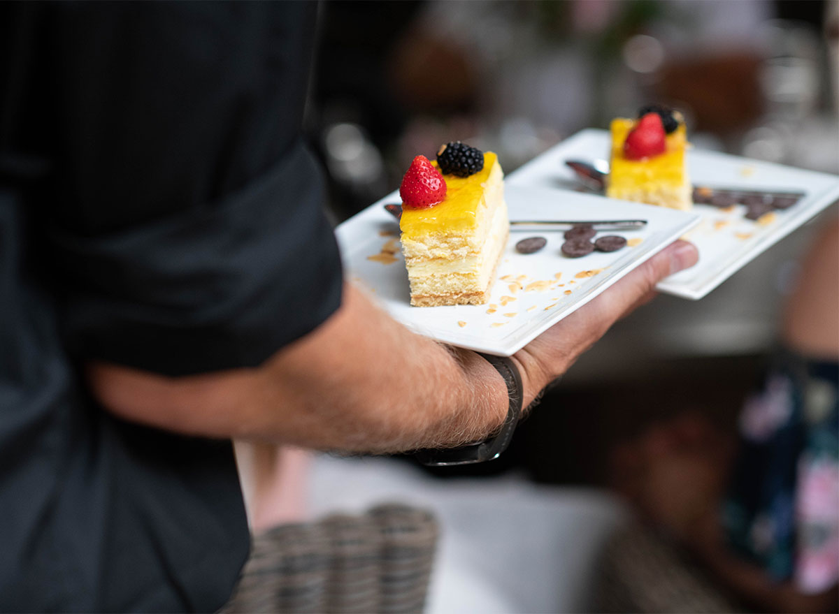 waiter carrying two cake slices
