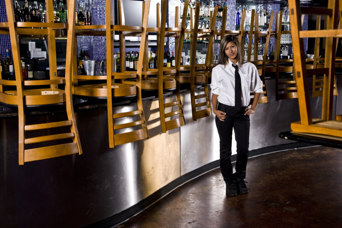 Worker standing next to bar of closed restaurant