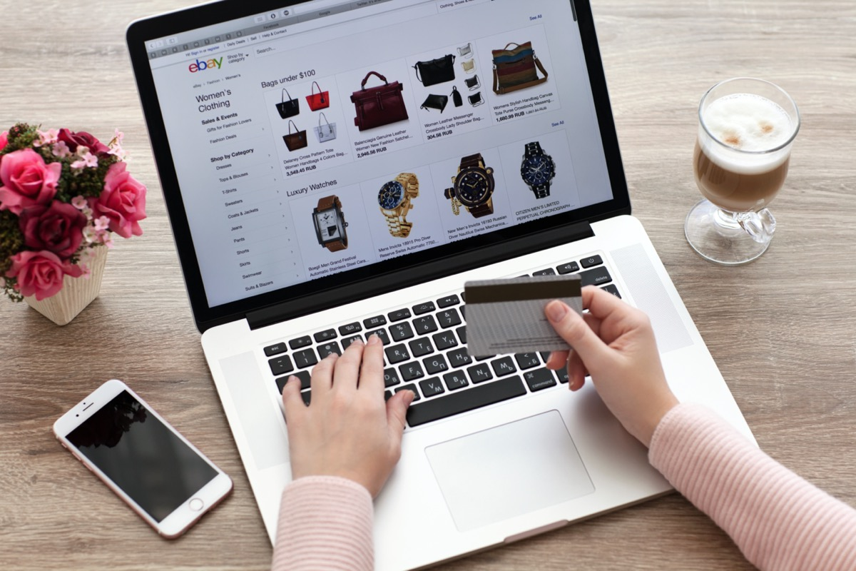 Woman with MacBook and iPhone Internet shopping service eBay on the screen
