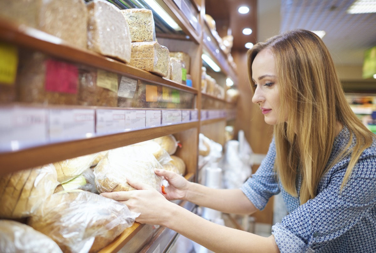 Woman holding loaf of fresh bread
