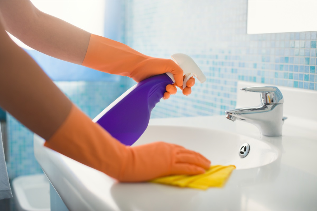 woman doing chores in bathroom at home, cleaning sink and faucet with spray detergent.