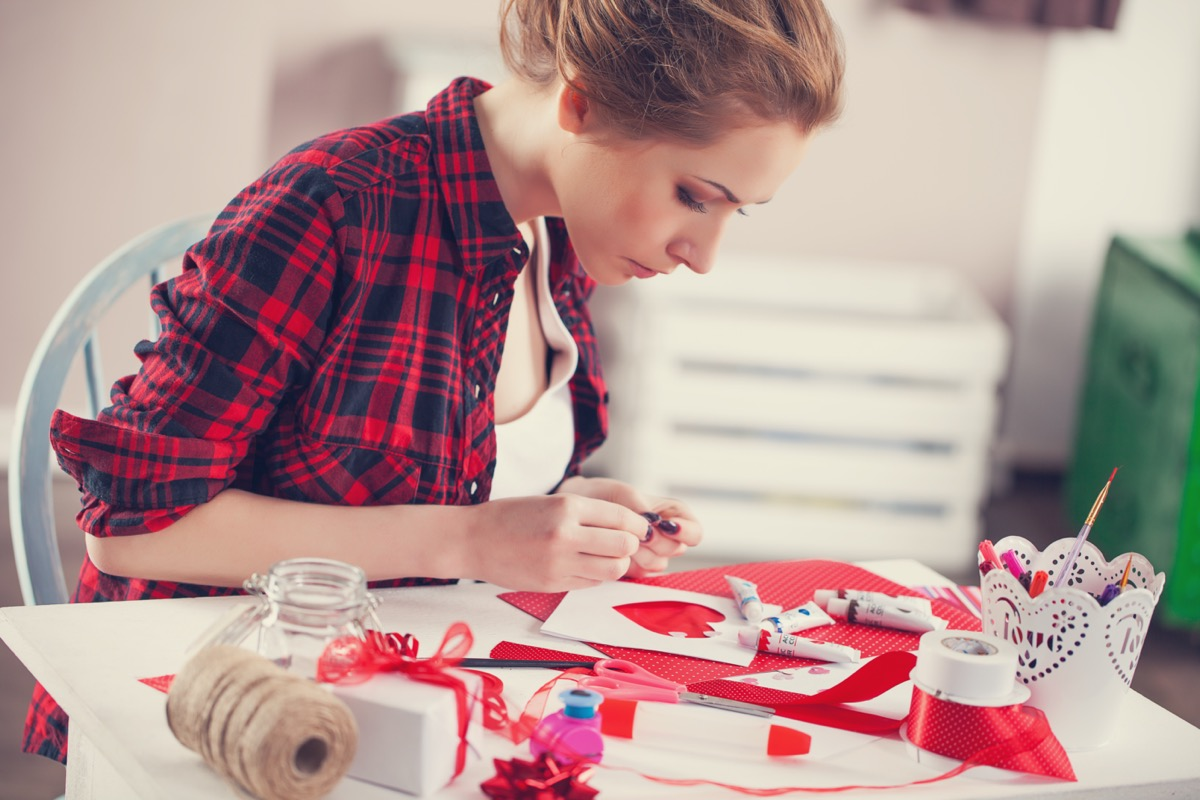Woman creating gift at home with paper and gouache