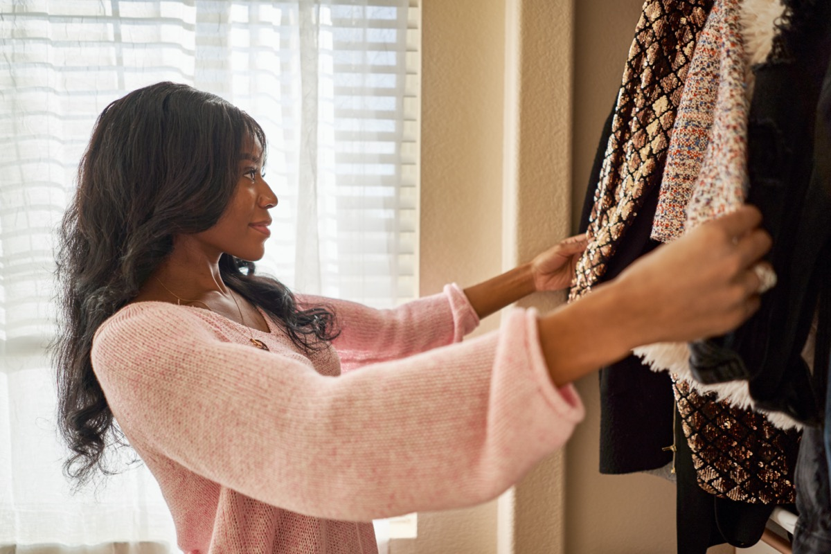 african american woman looking through closet in bedroom at home