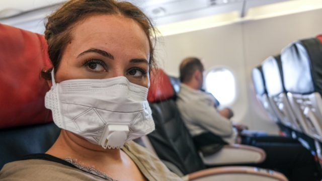 Woman Traveling with Plane with a Mask on For Contagious Disease