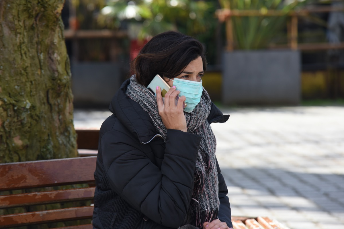 A brown hair girl sitting in a public park wearing protection mask calling friends and family for updates and news with her mobile phone