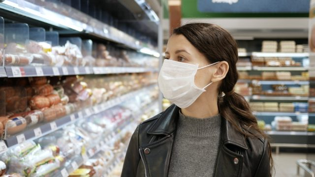 Young woman shopping in grocery store for food while wearing mask and preventing spread of coronavirus virus germs by wearing face mask.