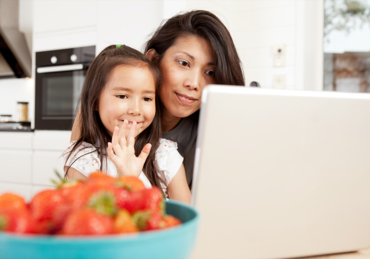 Mother and daughter using computer, waving while in a live video chat