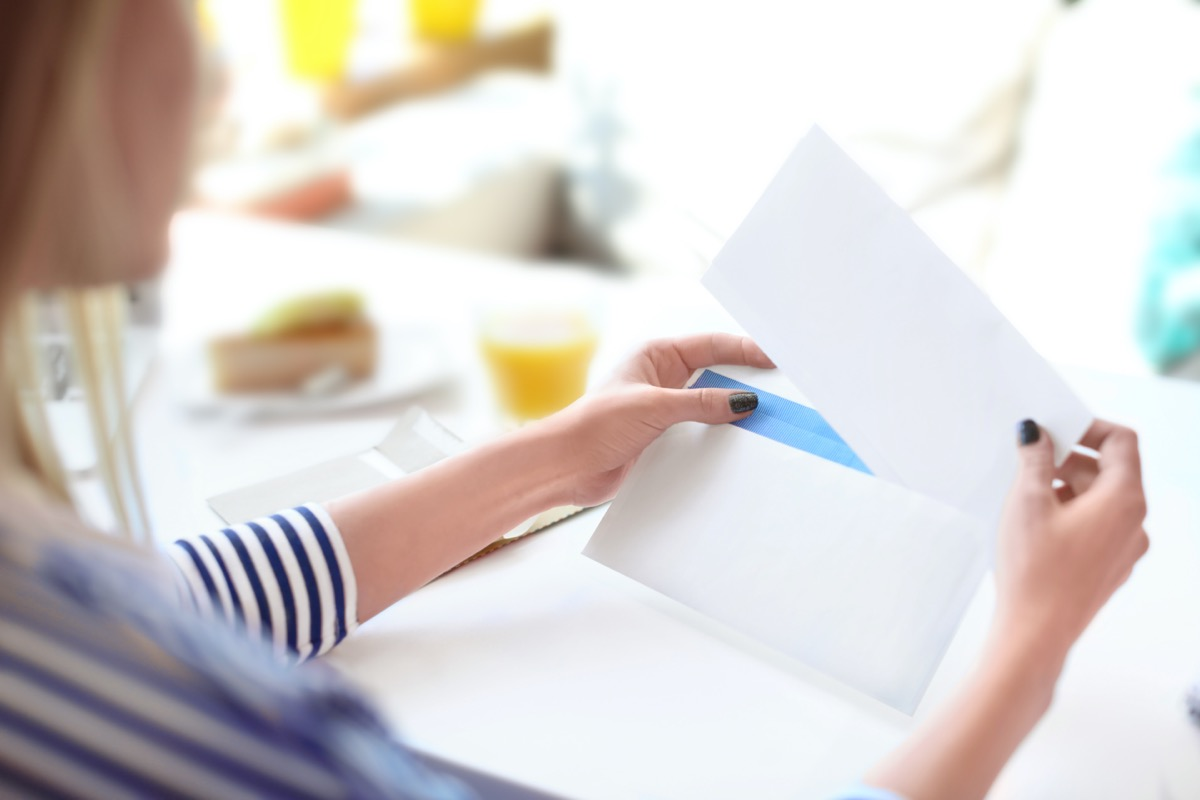 Young woman putting letter into envelope at table in cafe. Mail delivery