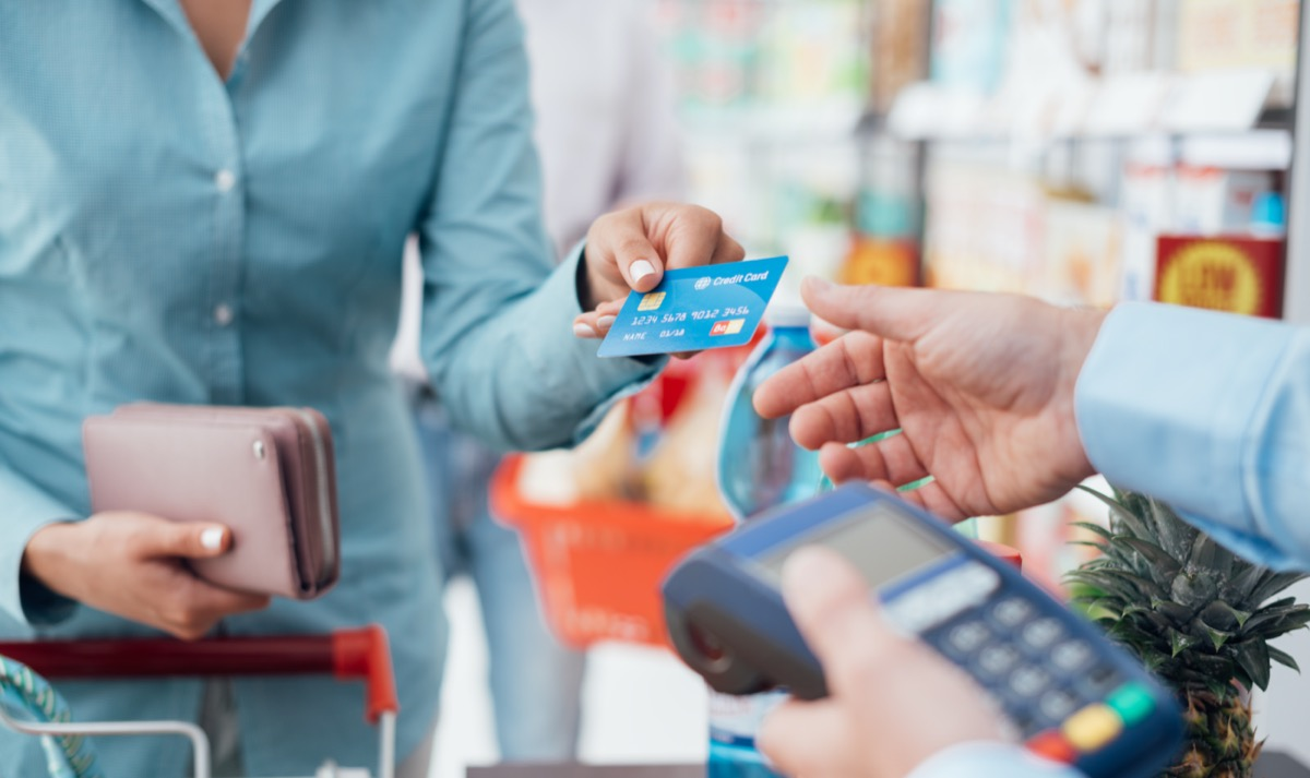 Woman at the supermarket checkout, she is paying using a credit card
